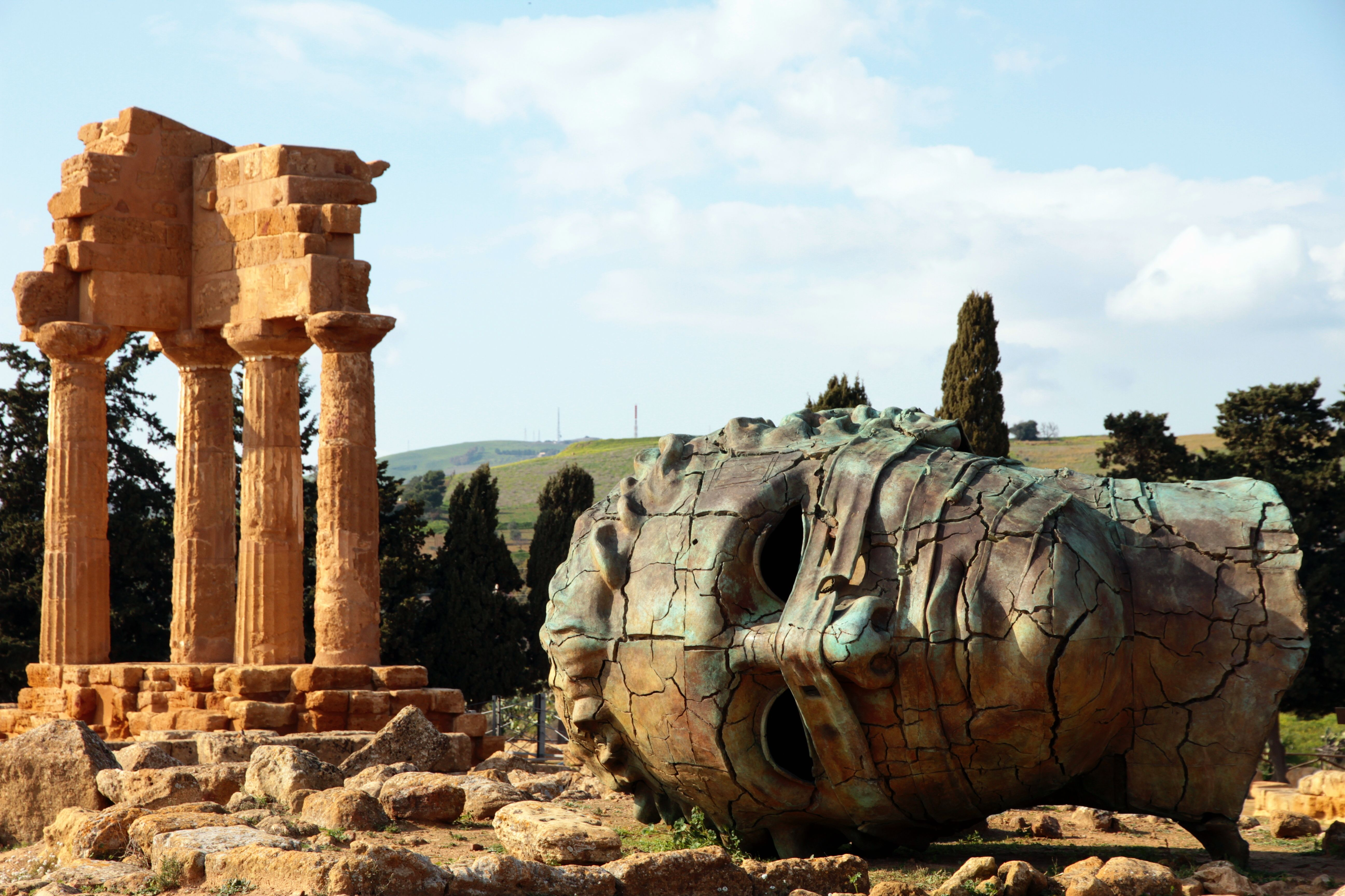 Bronze head of  a colossus statue in front of the Castor and Pollux ancient greek temple ruins at the archaelogical site of the Valley of the temples located at Agrigento, Sicily. Italy.