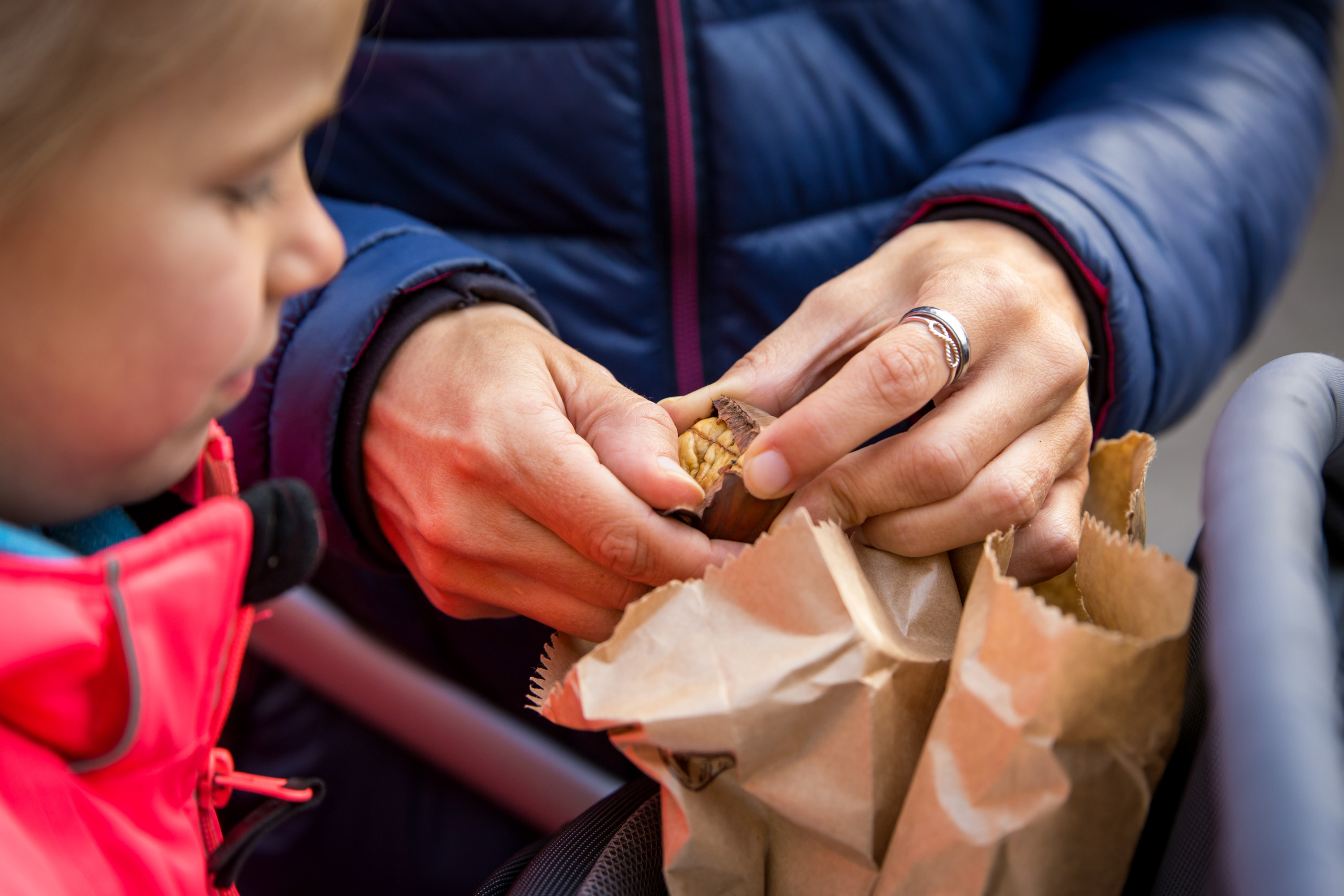 mother opening a roasted chestnut from a sale on a market, child looking on; Shutterstock ID 750864481; Purchase Order: FdW 5 - Juli; Job: ; Client/Licensee: ; Other: