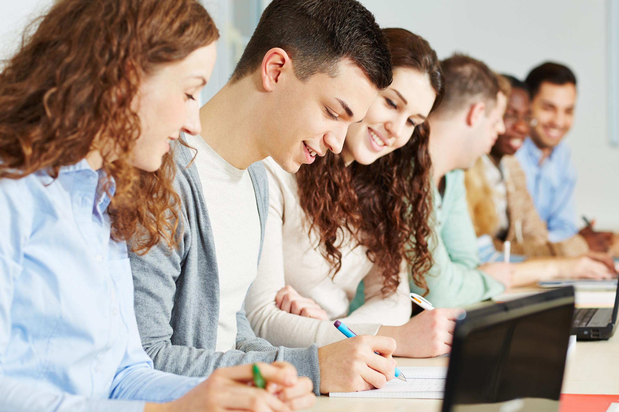 Lachende Schüler sitzen gemeinsam im Unterricht an einer Schule