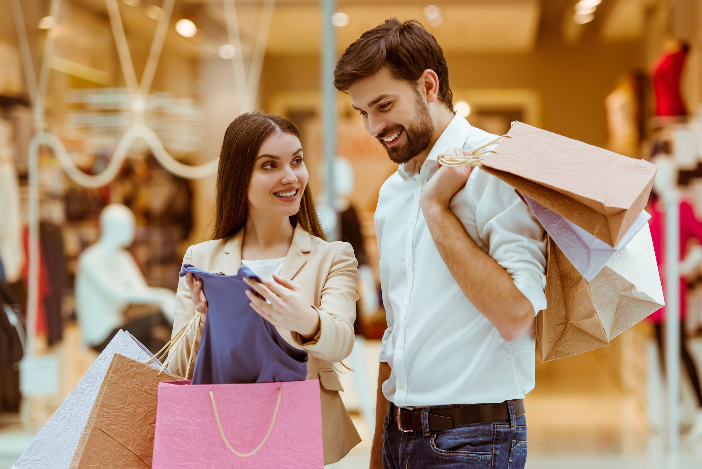 Happy beautiful young couple looking upon their purchase and smiling while standing in mall; Shutterstock ID 383258602